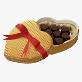 heart shaped box with chocolate and ribbon tied round with bow