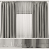 Wide gray curtains with white tulle and roman blinds.