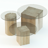 A set of coffee tables of stumps with a glass tabletop.