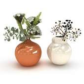Two flower arrangements in white and orange ceramic vases
